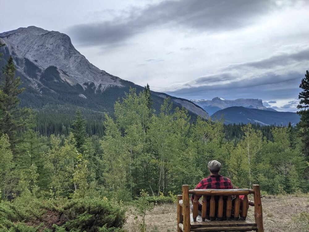 JR is sat with his back to the camera, on a wooden bench looking out to cloudy skies, and a prominent mountain peak to the left. There is forest in the foreground