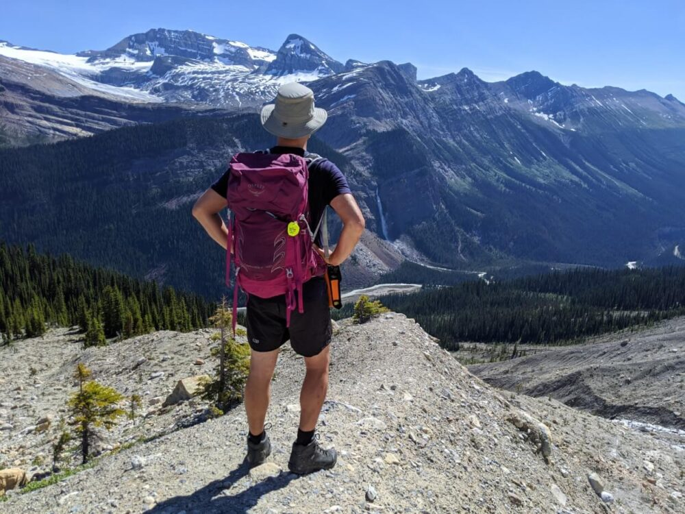 Back view of JR standing with pink backpack, looking out to views of snow capped mountains, glaciers and cascading waterfall across valley