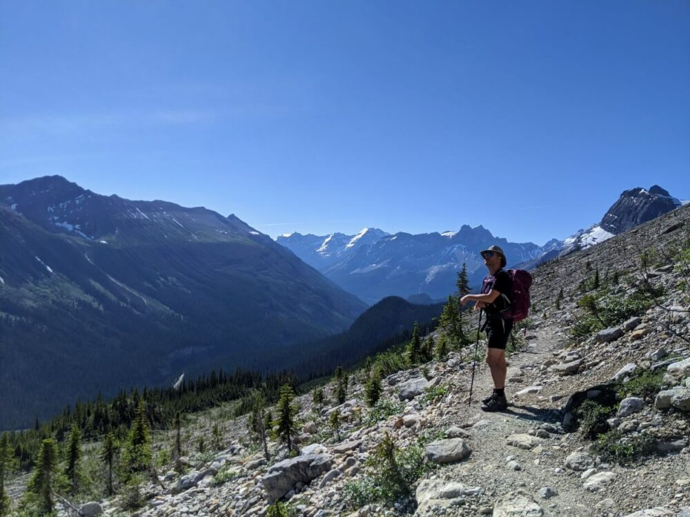 JR is standing on Iceline hiking trail, with backdrop of mountains and glaciers