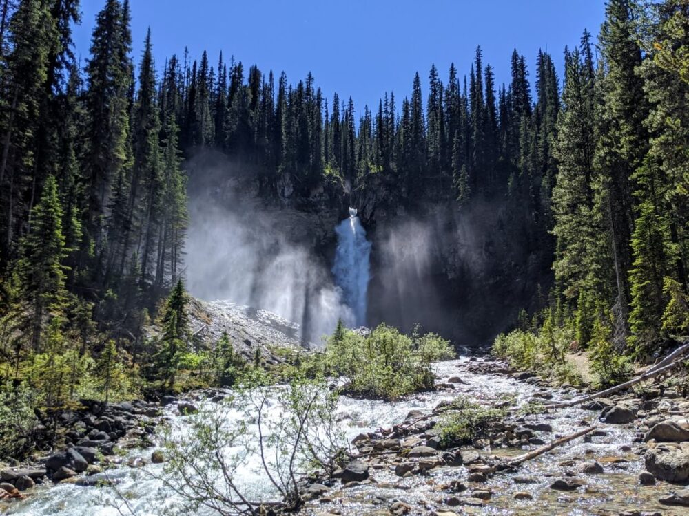 Looking up at cascading waterfall, surrounded by forest