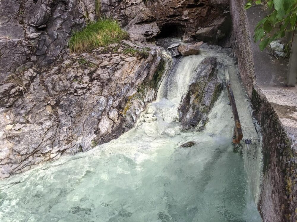 Front view of rushing stream flowing from cave at Miette Hot Springs source