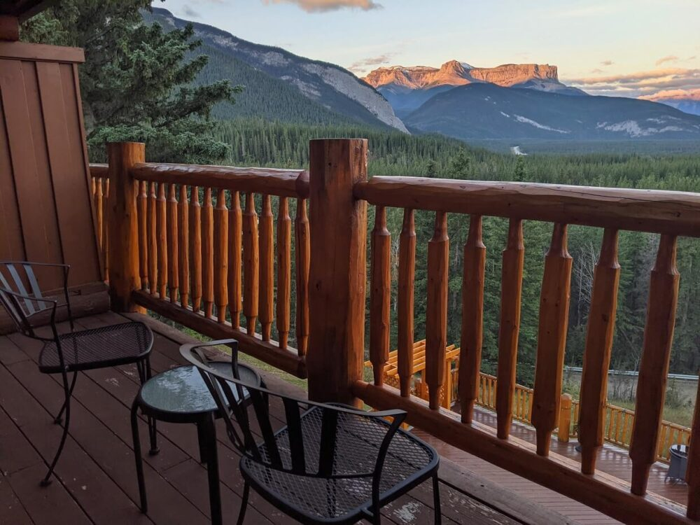 Side view of balcony at the Overlaner with two chairs and a table, looking out to mountainous views