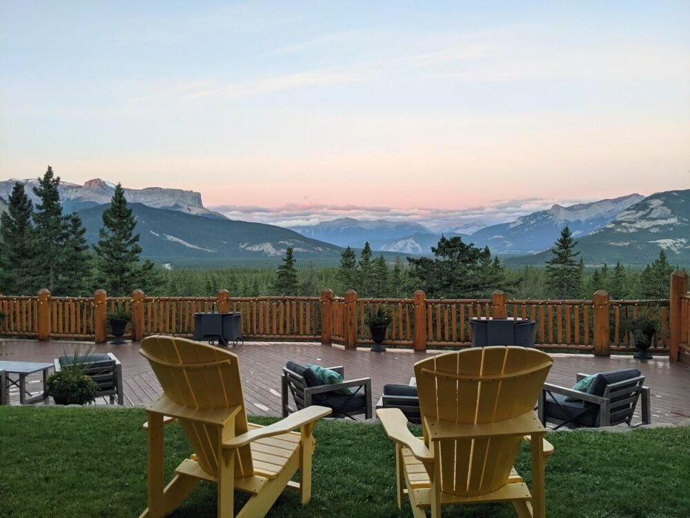 Back view of two yellow Adirondack chairs, looking out to sunrise views at the Overlander Lodge, with pink colours over the mountains