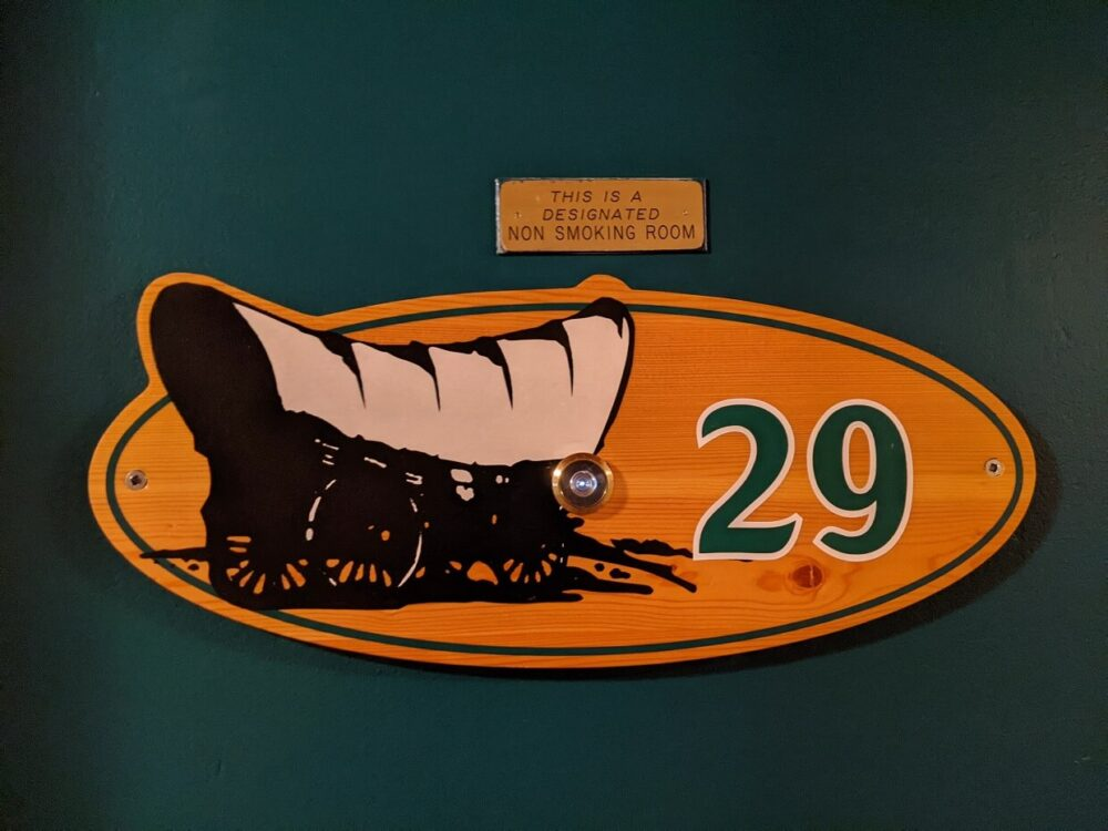 Close up of room number sign, with Overlander wagon imagery