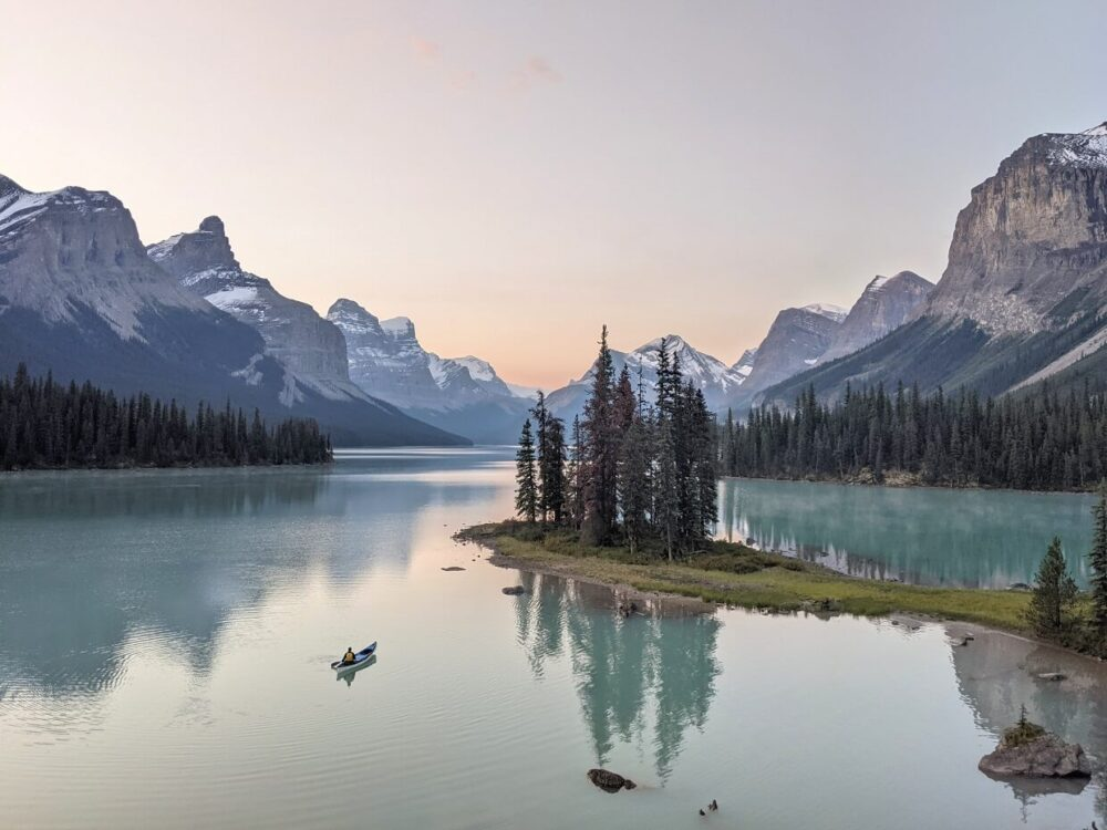 Looking across to Spirit Island (a peninsula with collection of trees), where a canoeist paddles across from the shore. Spirit Island surrounded by towering mountains