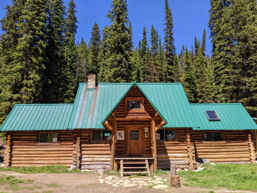 Front view of Stanley Mitchell Hut, a two story log cabin building with a green roof, surrounded by forest