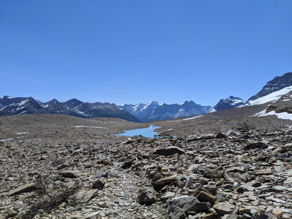 Looking across rocky moraine area towards turquoise alpine tarn, with mountainous backdrop