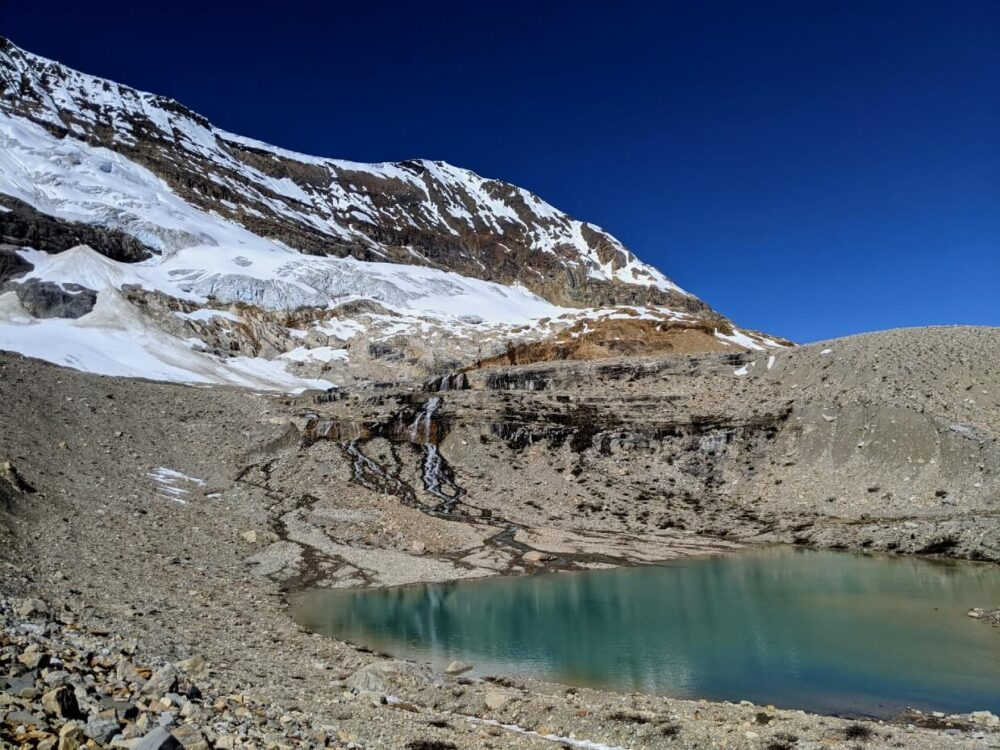 Side view of turquoise alpine tarn with glacier in background. There are a number of waterfalls leading from the glacier to the tarn pool