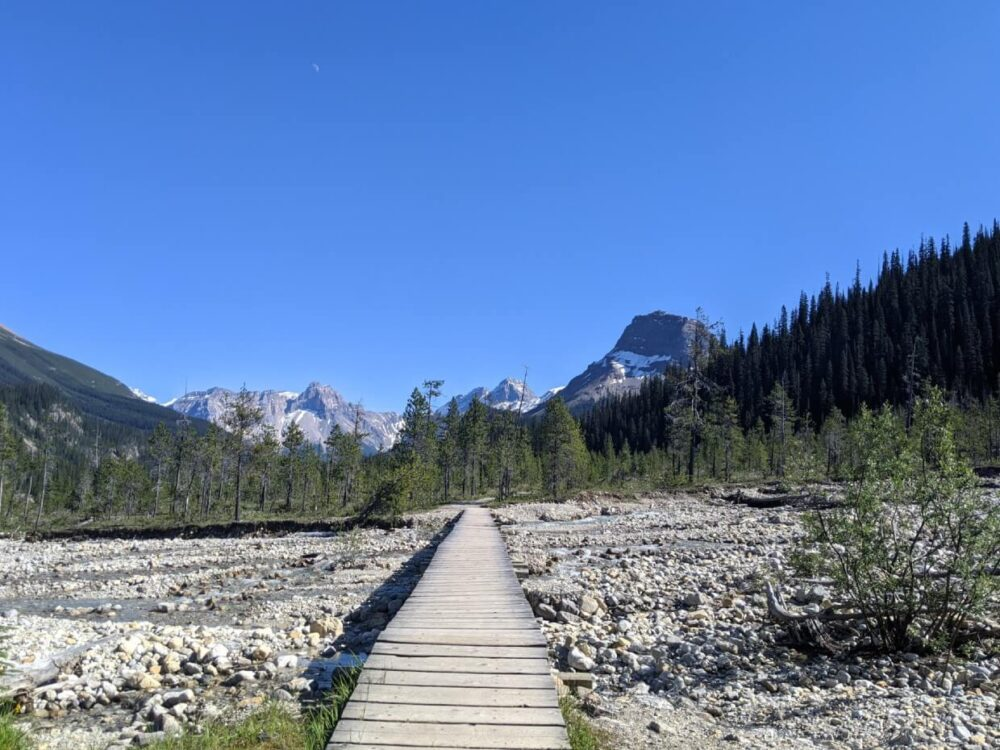 A boardwalk stretches from camera across rocky river towards mountainous landscape