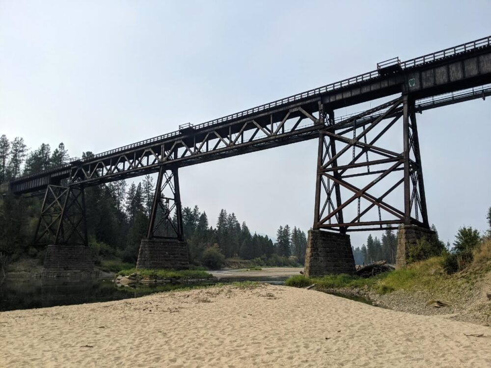 Looking up to a large railway trestle above a river and sand bank