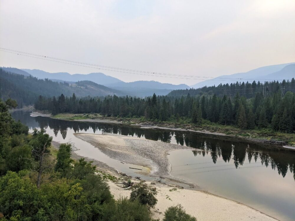 Smitten Trestle views across the Kettle River towards the US. The river is wide, with sand island in the middle and lined by forest. There is smoke in the air