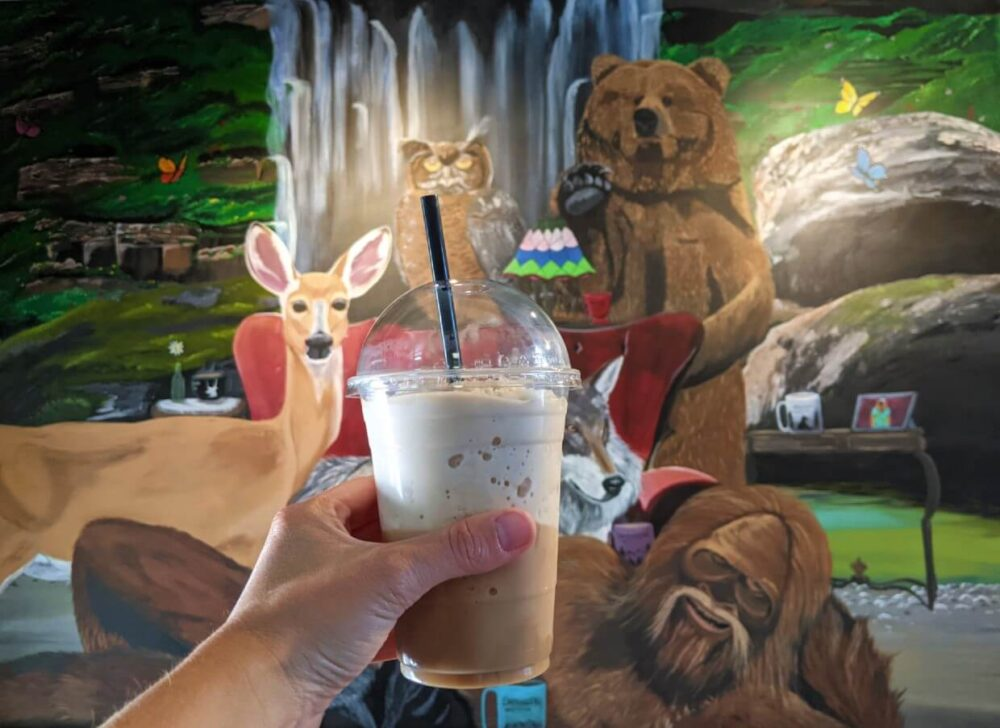 A cold coffee drink is held up in front of a mural featuring big foot, a grizzly bear, owl and deer