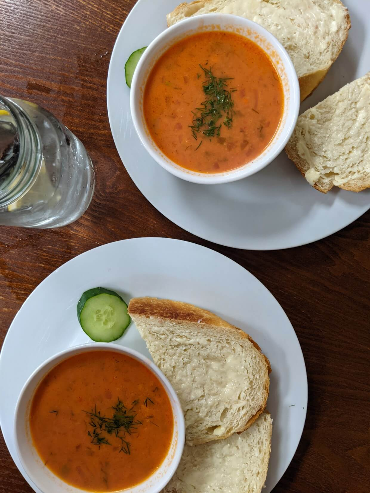 Overhead view of Borscht Bowl meal, with two bowls of orange coloured borscht, buttered bread, cucumber and a glass of water