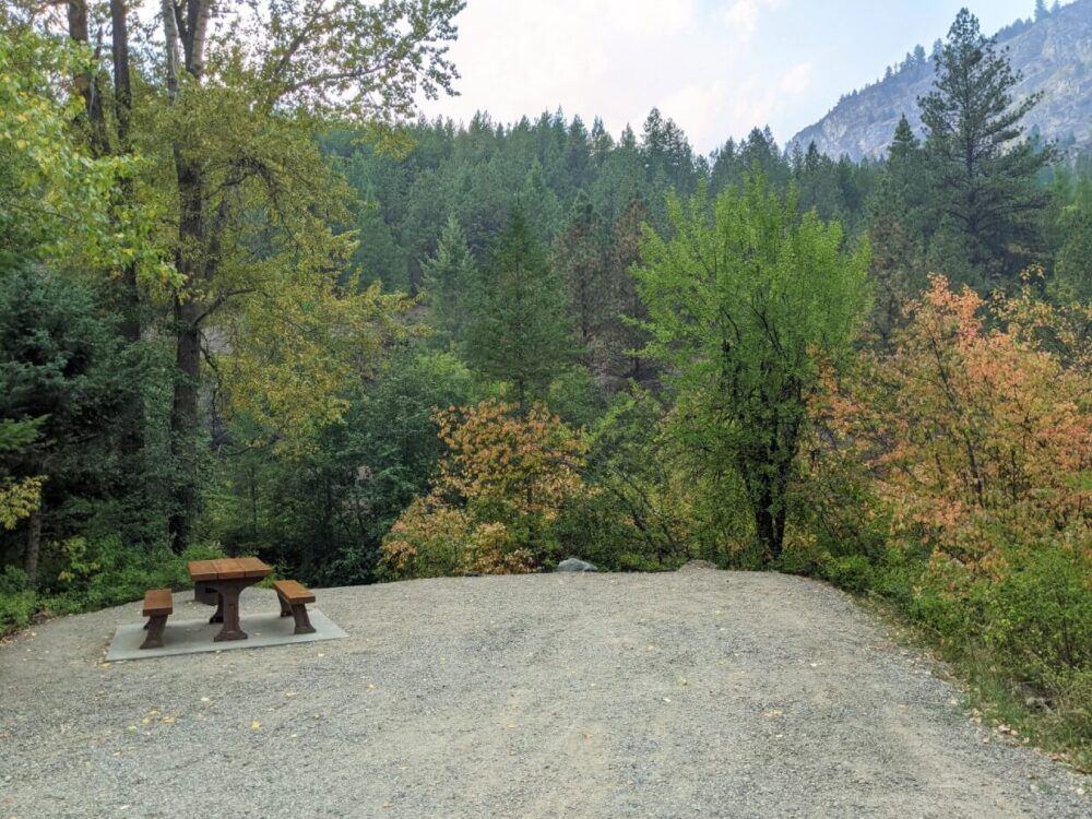 View of Boundary Creek Provincial Park campsite with picnic table on cement square, with fire pit behind. The campsite is surrounded by trees, some of which are changing colour