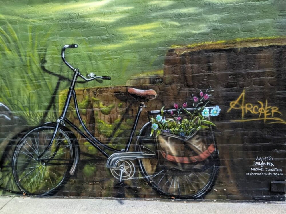 Painted mural on brick building, of bicycle with flowers in bag on back tire. The artist name (Archer) is on the right