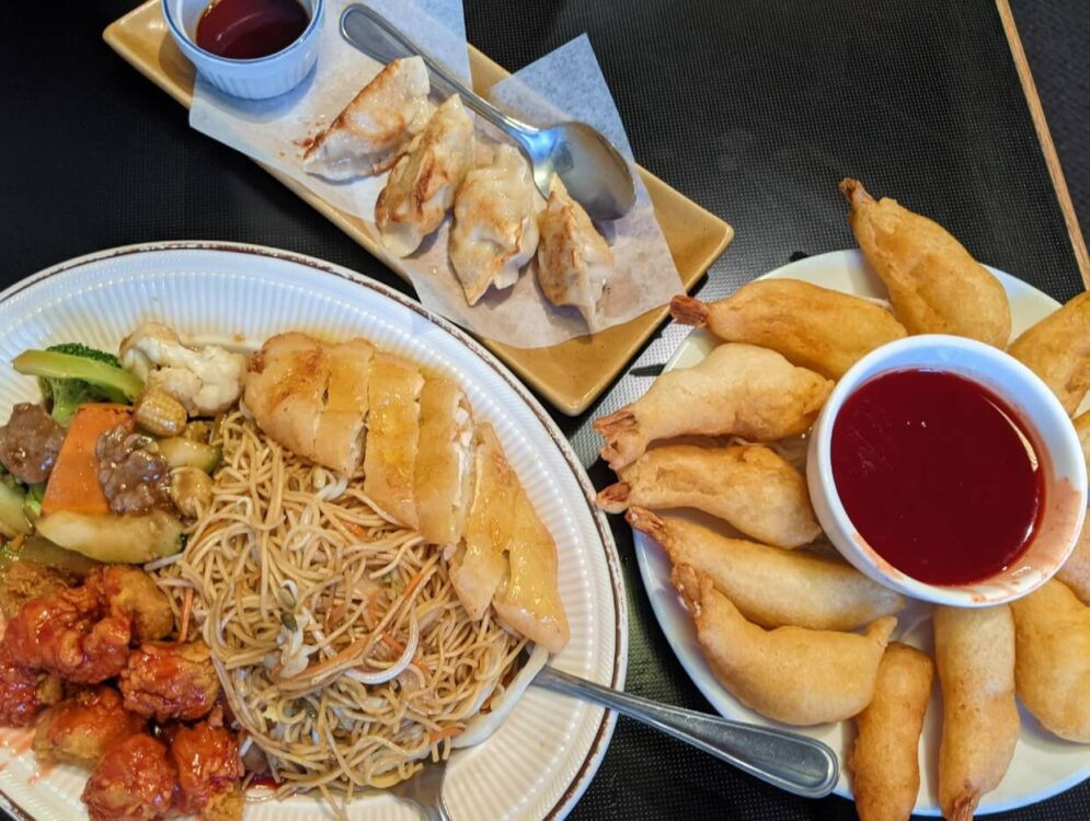 Overhead view of Chinese food at the Golden Chopsticks, with combination plate of noodles and pork plus deep fried prawns and dumplings
