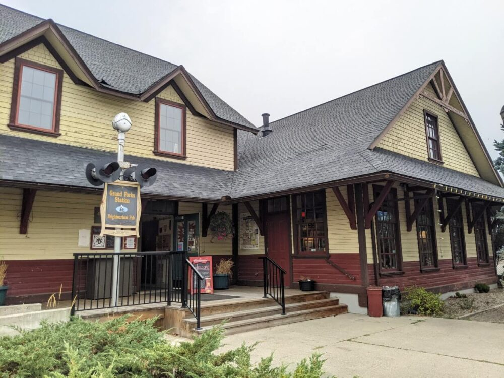 Front view of Grand Forks Station Pub, a two story heritage building (the original Grand Forks building0. The building has yellow and red panelling and a sloped roof