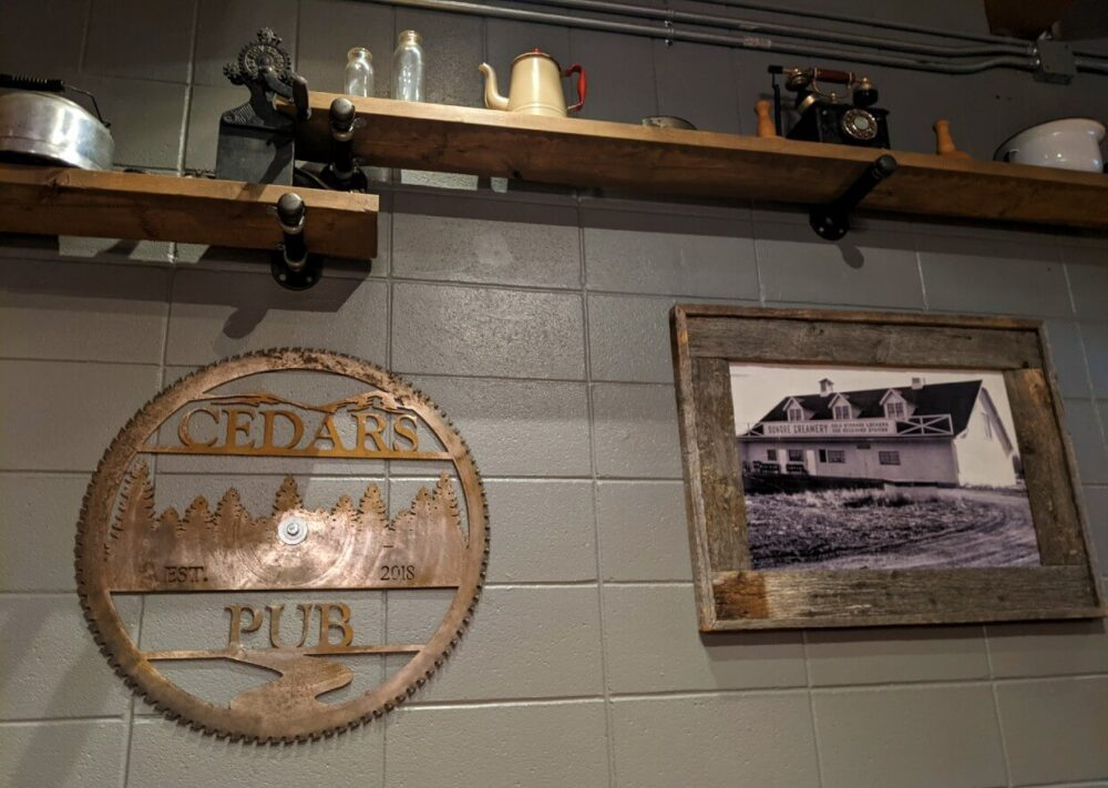 Wall decoration at Cedar's Pub featuring a framed photo of a farmhouse, a decorative saw with the pub name and shelving with other household items