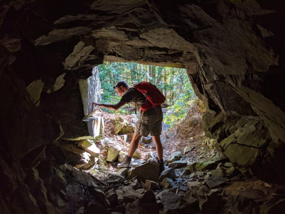 View from inside mine entrance looking back at JR in entrance, turned to the side and looking at inscriptions on rock