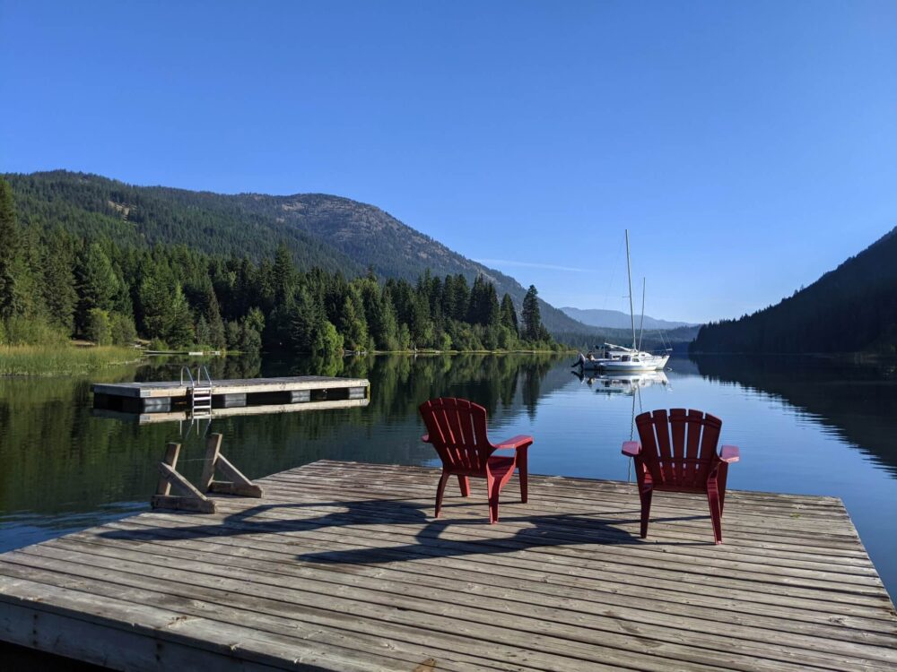 Back view of deck at Jewel Lake Resort, with two red Adirondack chairs facing lake. There is a swimming platform and boat on the lake