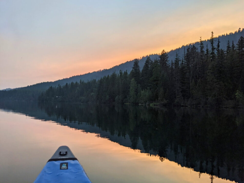 Sunset view of Jewel Lake from canoe, with orange colours behind mirror like reflections of lake and forest