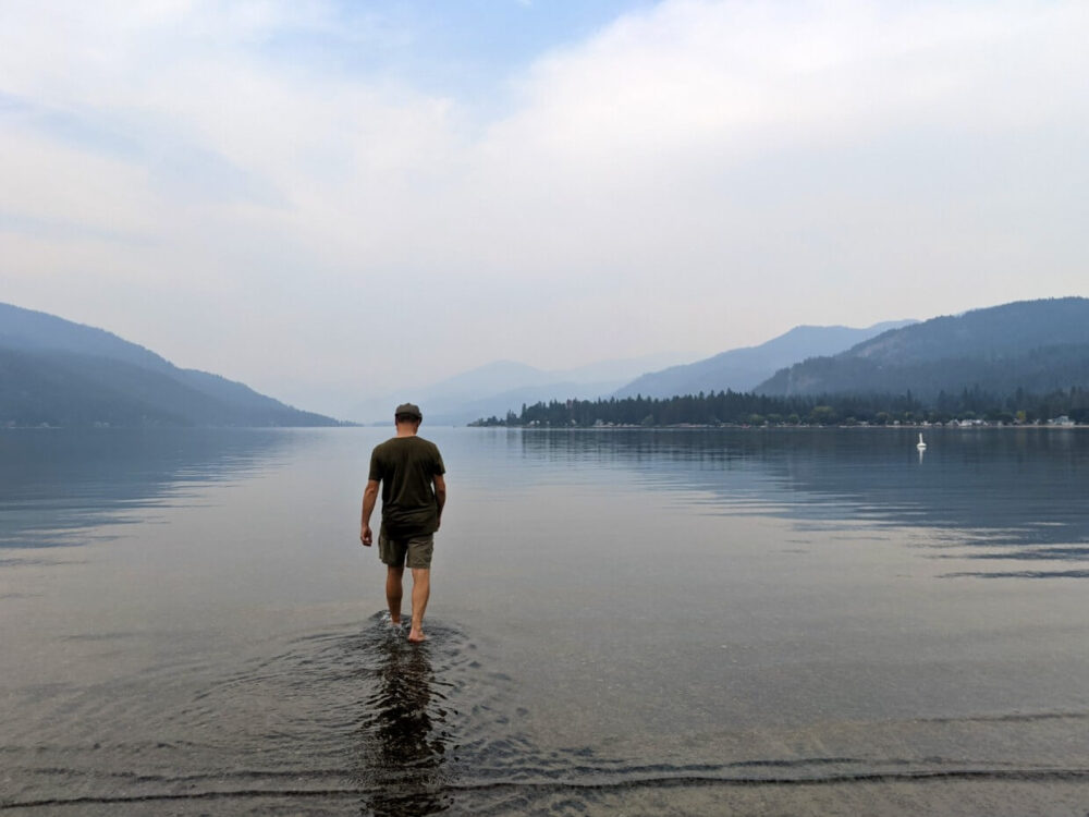 Back view of JR walking out onto Christina Lake. There air is smoky but hills are visible in the background