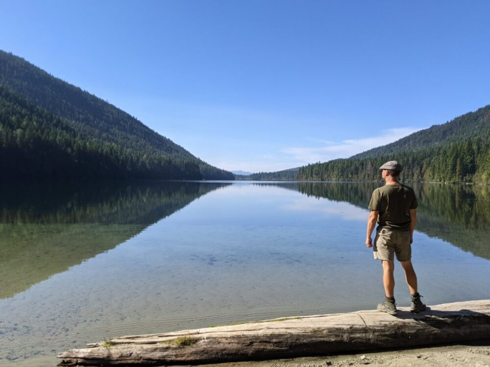 Back view of JR standing on a log looking out to view of calm Jewel Lake on sunny day