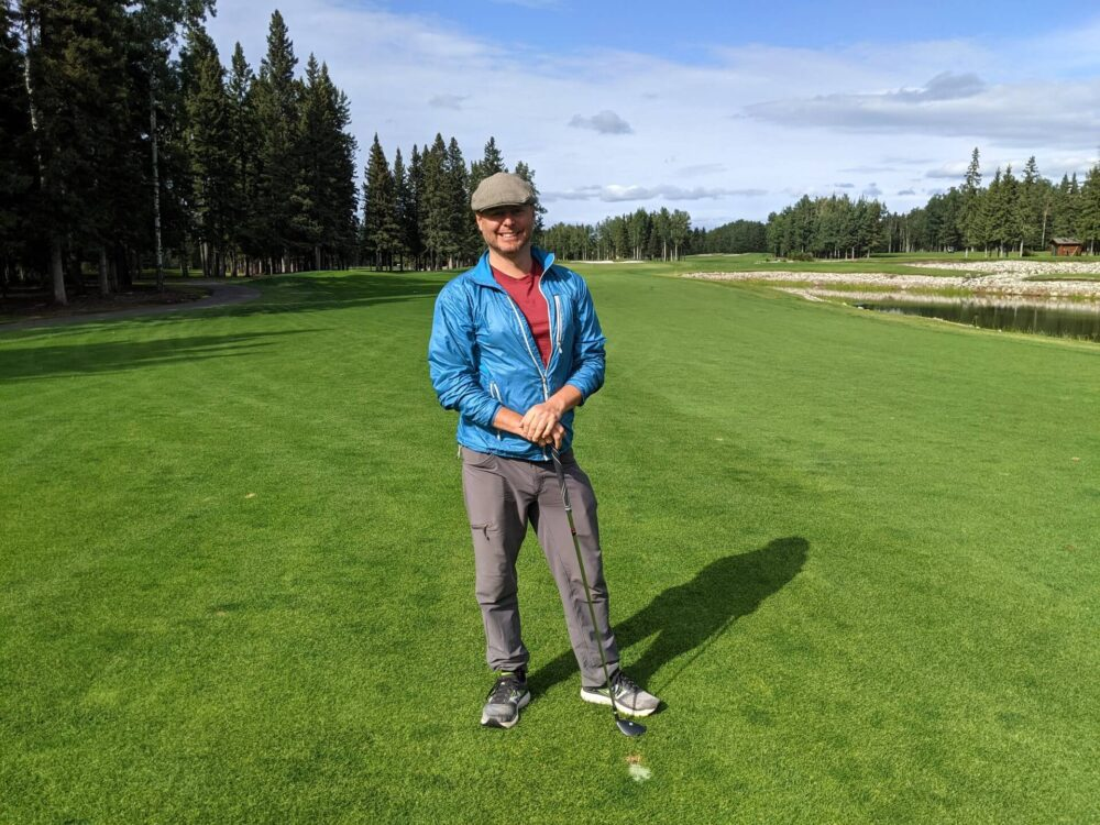 JR faces the camera standing with a golf club at Sundre Golf Club, on the green