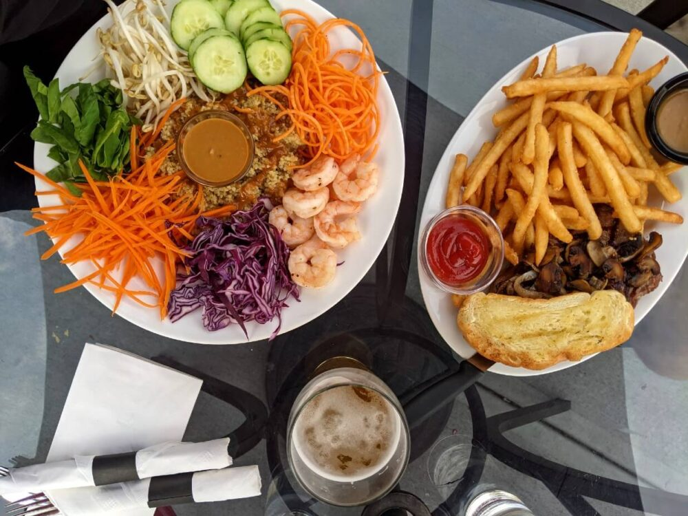 Overhead view of meal at Keg and Kettle Grill, with a quinoa plate (prawns, veggies) and a steak with garlic bread and fries. There is a beer and cutlery between the plates