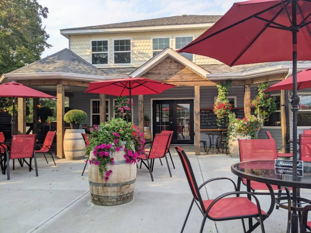 Front view of two story Keg and Kettle Grill building, with large patio featuring red seating and umbrellas