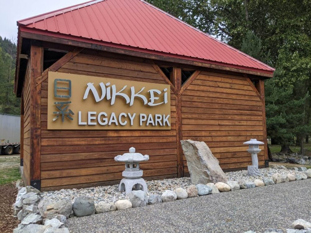 Side view of Nikkei Legacy Park, with wooden shelter, white Japanese sculptures