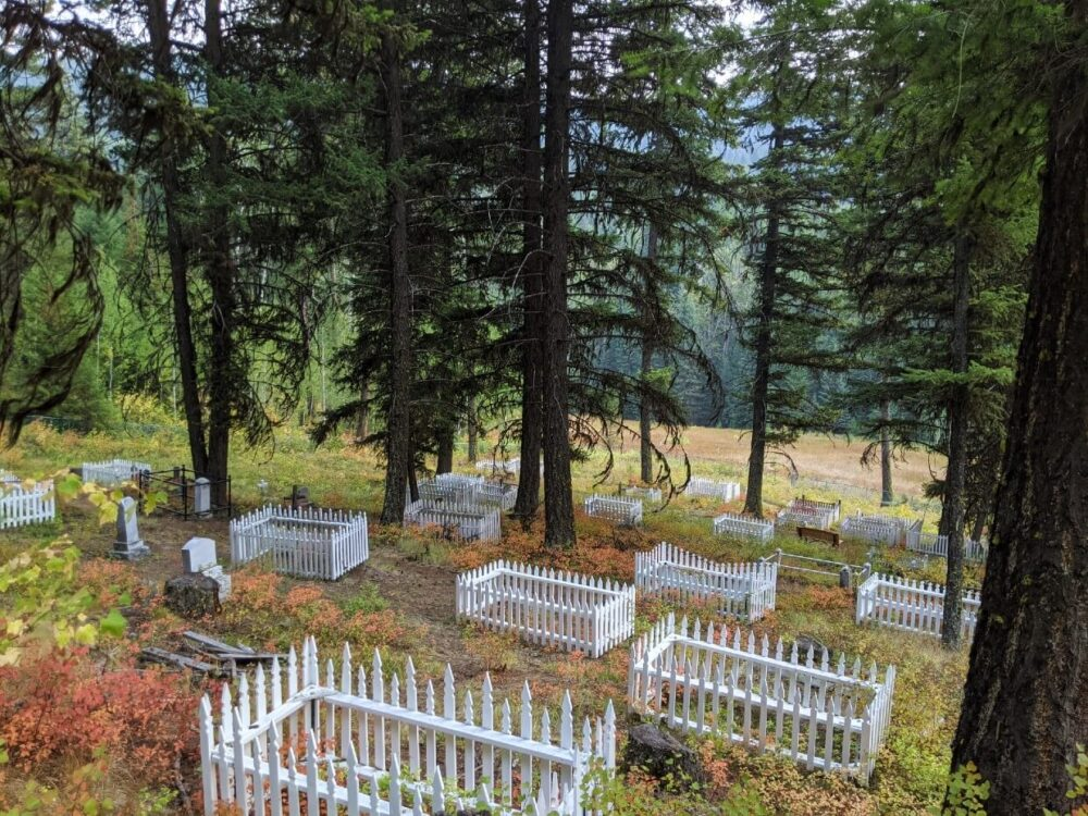 Elevated view looking down of cemetery on Phoenix Mountain, with white fences around graves, red coloured bushes and trees