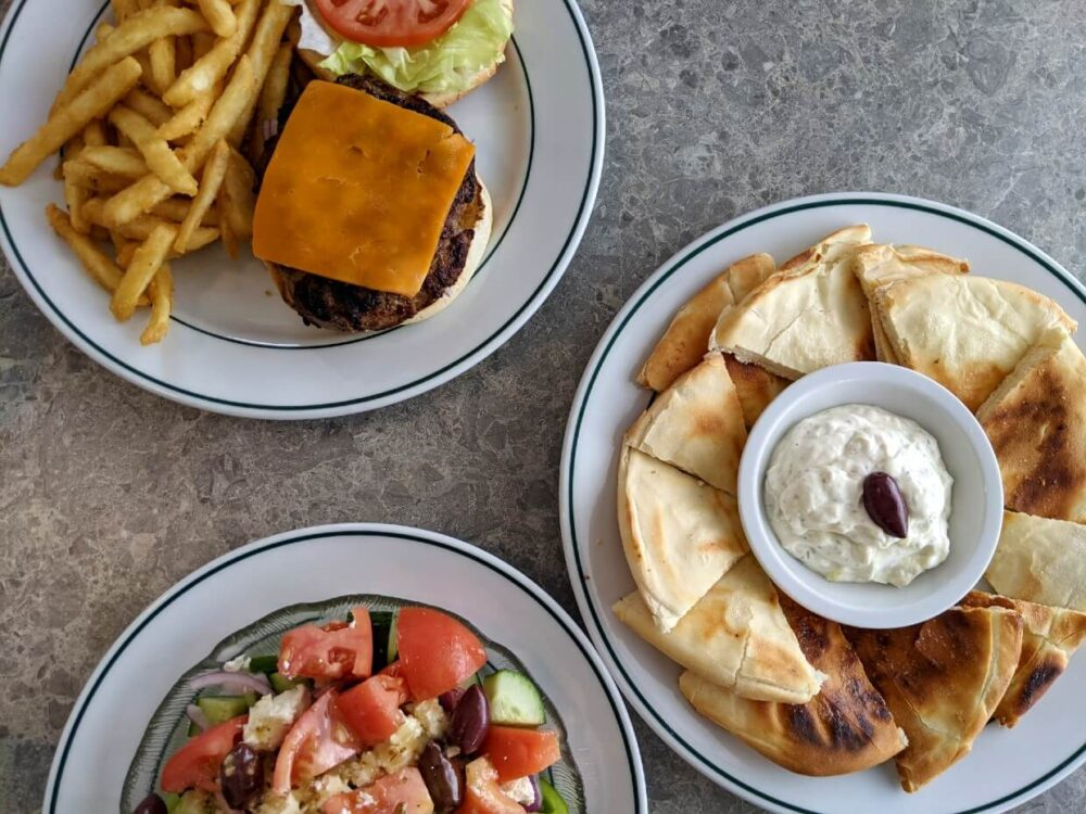 Overhead view of three fishes at Piro's - Sirloin burger, greek salad and tzatziki dip with pita bread