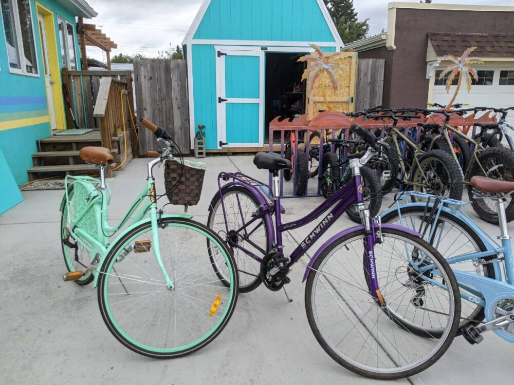Side view of bikes lined up outside blue coloured house in Sundre