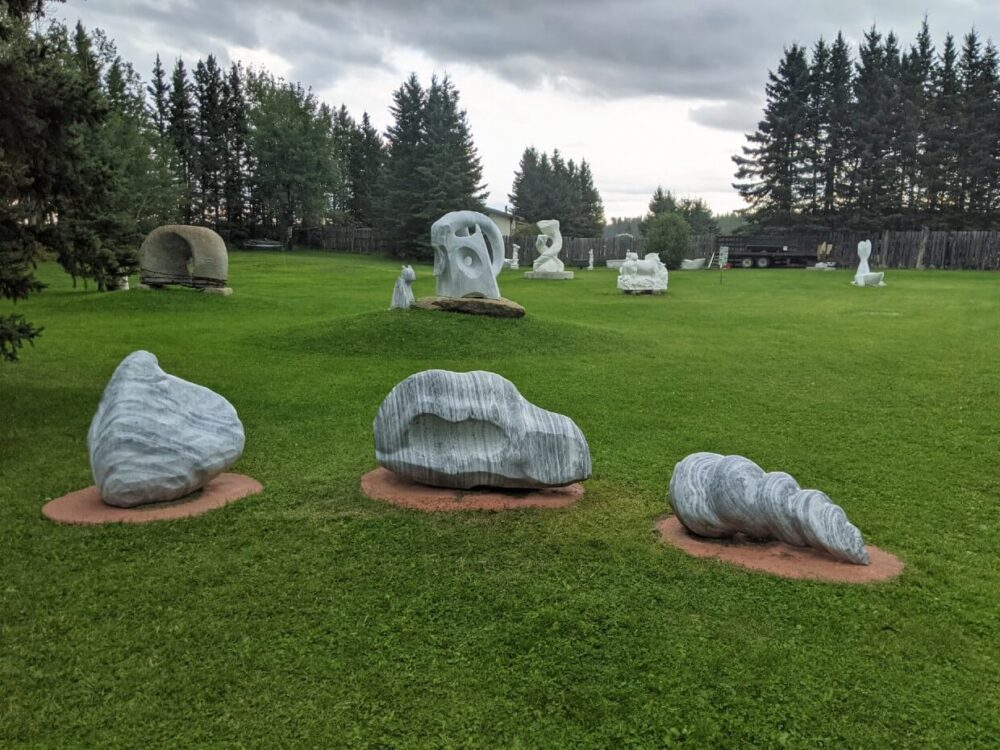 Front view of marble sculptures in park area, with other marble sculptures visible in the background.