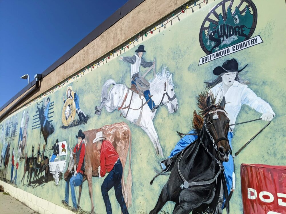 Close up of painted mural on wall in downtown Sundre, showing horse riders and rodeo imagery