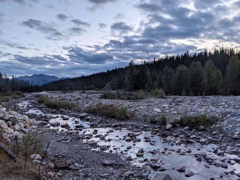 Late evening photo of river with mountainous terrain in background and forest bordering rocky banks