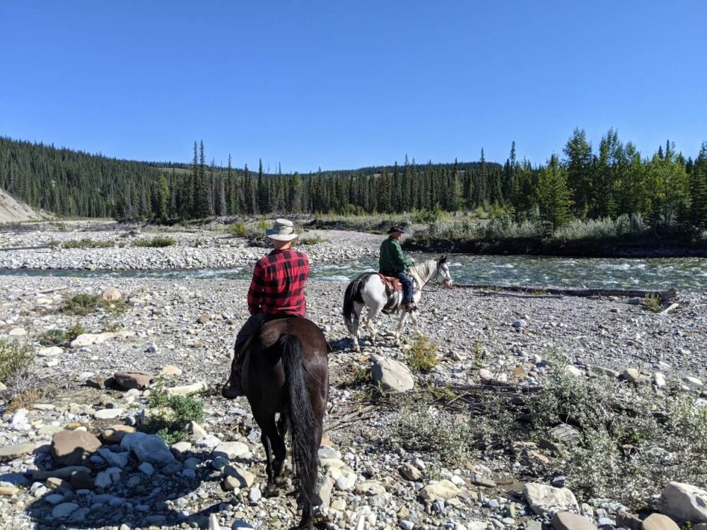 View from horse of JR riding brown horse ahead, with guide on white horse ahead on right, approaching river surrounded by rocky banks