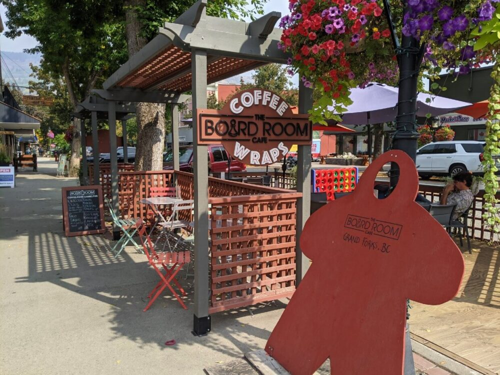 Side view of Board Room Cafe streetside patio with seating and signage. There are vibrant flowers on the street lamps