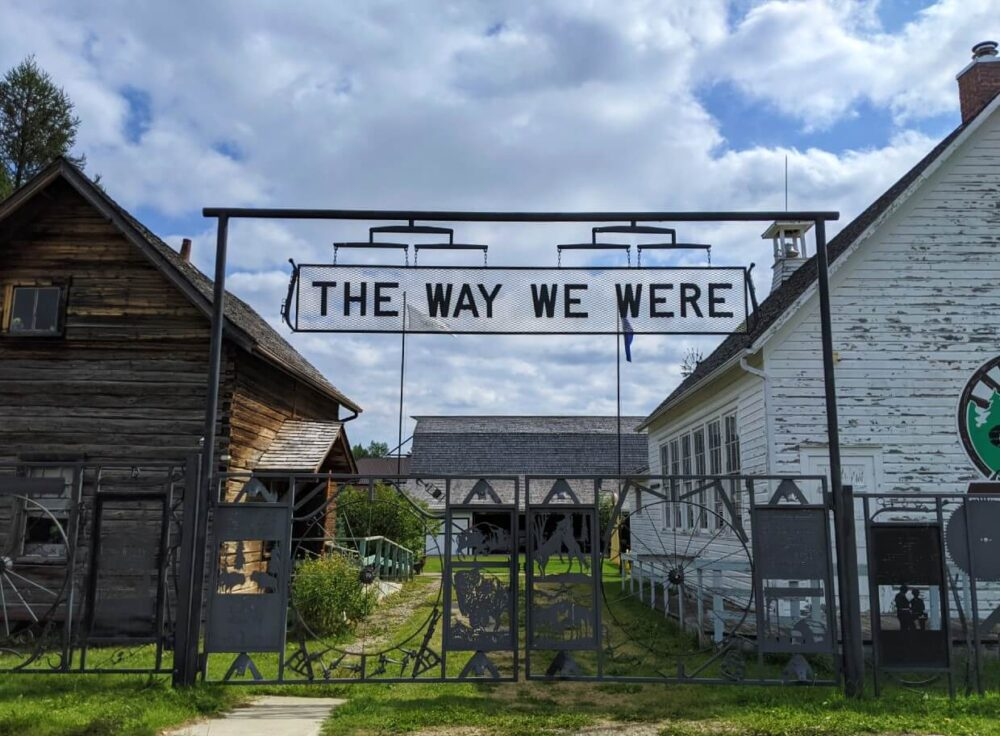 Metal gate with 'the Way we Were' signage in front of two heritage buildings at Sundre Museum