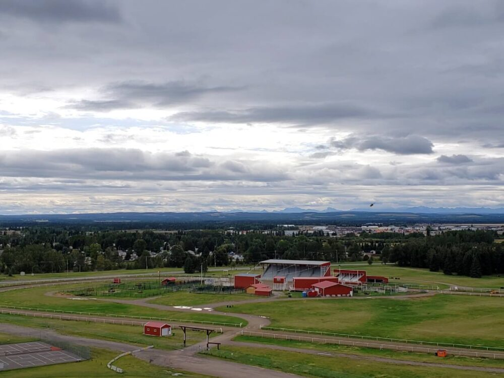 Viewpoint panorama of Sundre and surrounding scenery, including red rodeo grounds in foreground and rocky mountains in background