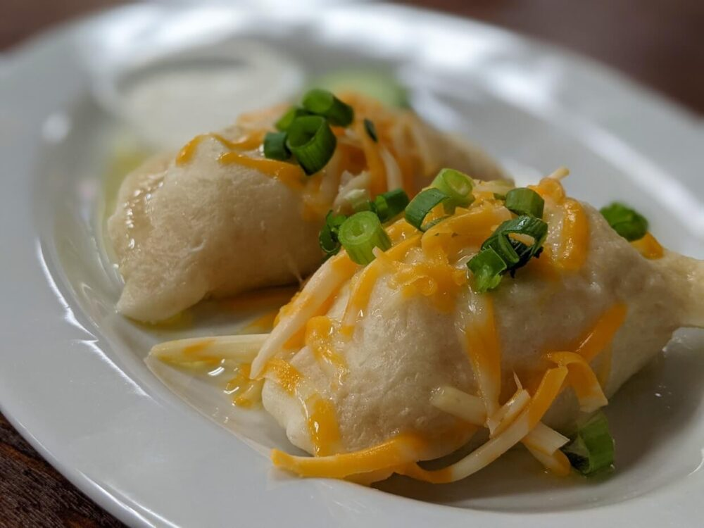 Close up of two large vareniki (similar to pierogis), covered with green onions and cheese