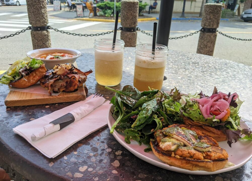 Looking over at Wooden Spoon Bistro meal on outside table, with two burgers on plates and two fruit smoothies behind. A fork in napkin sits between the plates