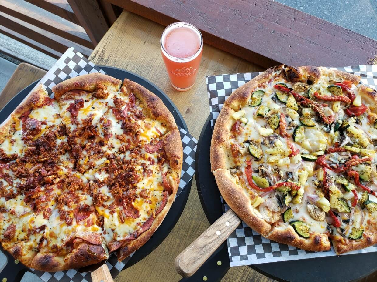 Overhead view of two pizzas and a beer at Mount Arrowsmith Brewing Company