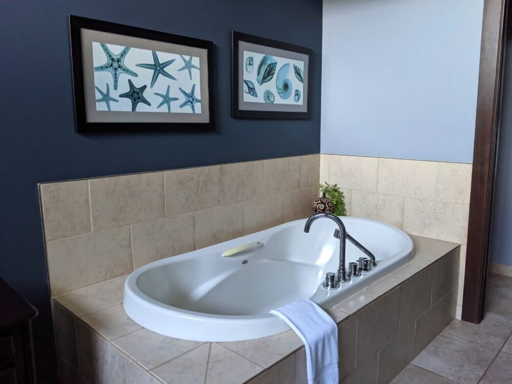 Large built in bathtub in Sunrise Ridge Waterfront Resort room, with framed pictures of starfish behind
