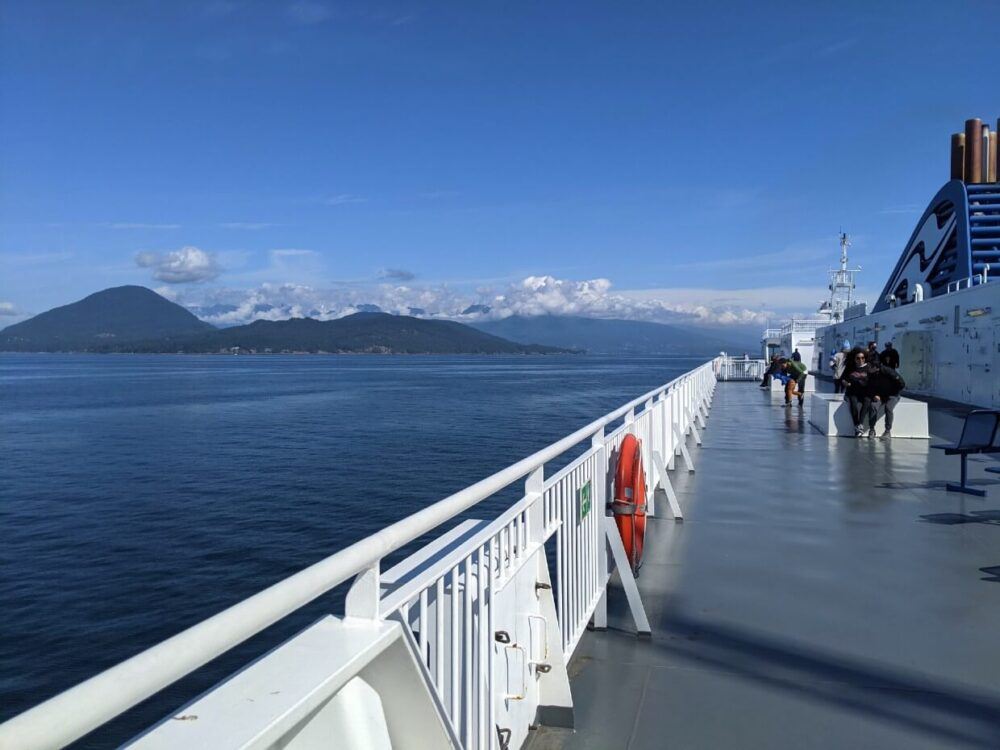 Sie view of BC Ferries deck with views of calm ocean and mountain behind