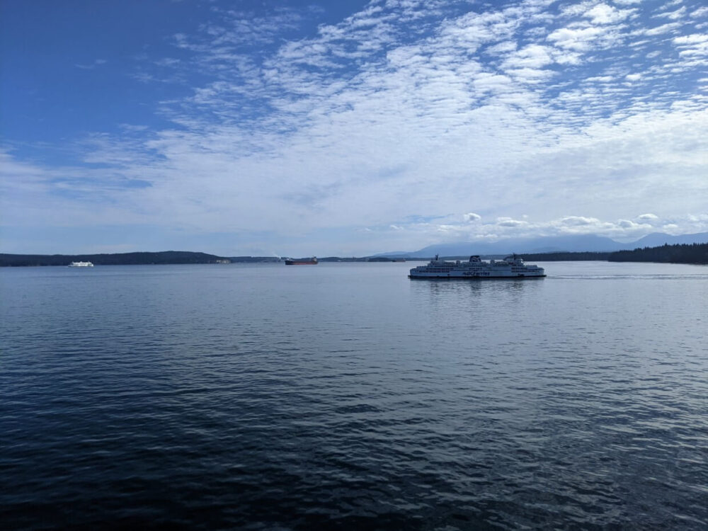 Looking out to Salish Sea with BC Ferries boats crossing in front of islands and mountin panoramas