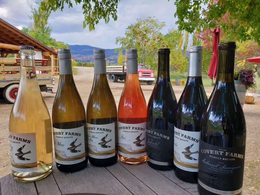 Seven bottles of Covert Farms lined up next to each other in front of farm trucks