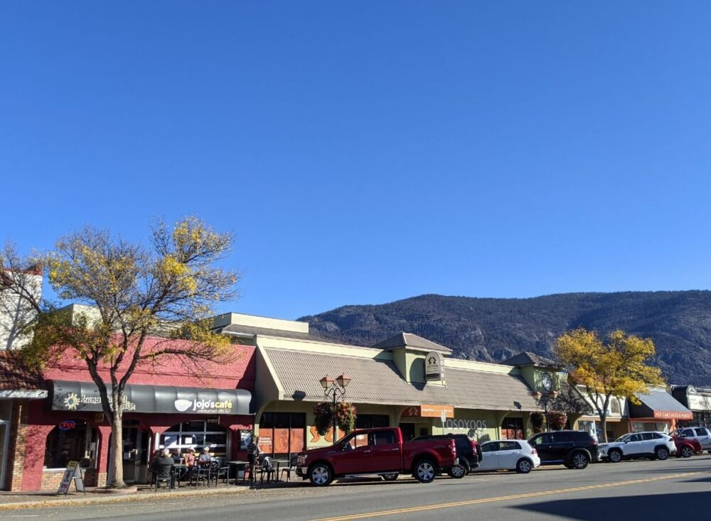 Sidewalk view of downtown Osoyoos with shops, cafes and parked cars on sunny day, with two yellow coloured trees