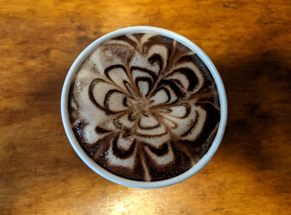 Overhead view of pretty flower pattern on hot chocolate at JoJos cafe